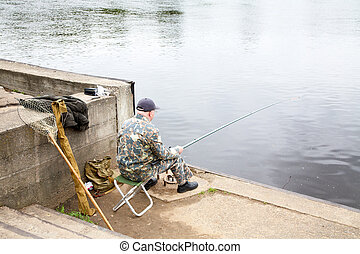The elderly man fishes