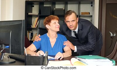 The elderly mother sits in the office at her desk. Her son a businessman hugs her from behind and smiles. family business. 4k. Slow motion.