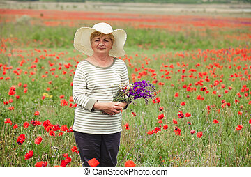 The elderly woman in a meadow with poppies