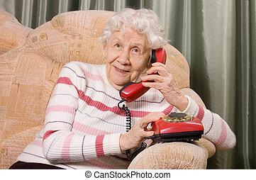The elderly woman speaks on phone - The elderly woman speaks...