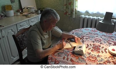 The elderly woman takes arterial blood pressure and records in a notebook