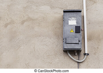 the electric meter on a concrete wall