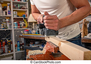 the electric sander on a wood backgroundshavings