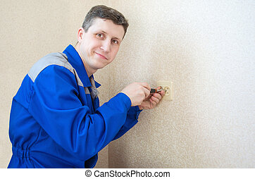 The electrician installs an electrical outlet