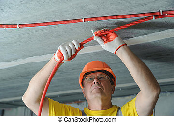 The electrician is fixing an electric corrugated tube. - The...