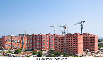 The elevating crane against the dark blue sky, building a...