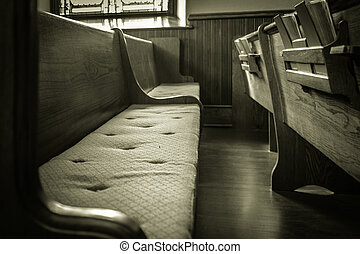 An empty wooden church pew in black and white.