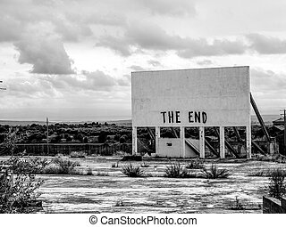 An old cinema billboard has the deep words of 'The End' painted onto a blank board, in a degraded parking lot.