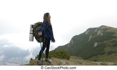 The end of adventure of successful explorer woman reaching the top of mountain looking around to amazing landscape