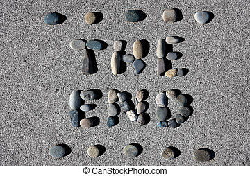 """The End"" spelled out in pebbles on beach sand"