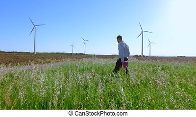 The engineer begins work with the drawings against the background of windmills
