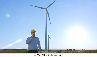 The engineer goes and talks on the phone against the background of windmills.
