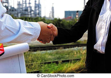 The engineer guy is shaking hands with construction manager.
