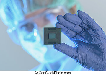 The engineer holds a processor in hands