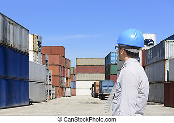 The engineer looking at the container stack at  ship yard with the blue sky waiting for export to international