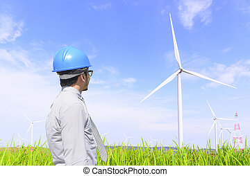 The engineer man looking to the wind turbine in the grass field with the blue sky