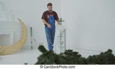 The engineer removes the cover-up from the metal trunk of artifisial Cristmass tree in the big white studio.