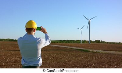 The engineer stands on the background of windmills and takes pictures