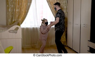 Happy adult dad is dancing with joyful dear baby in a large living room in home clothes. On against a bright window. They are masked