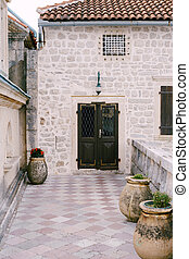 The entrance to the house is closed metal door with a grate through the yard with large pots for flowers.