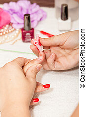 The esthetician removes the old nail polish with a cotton and remover