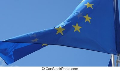 The EU banner waving optimistically windy weather in a blue sky in slo-mo