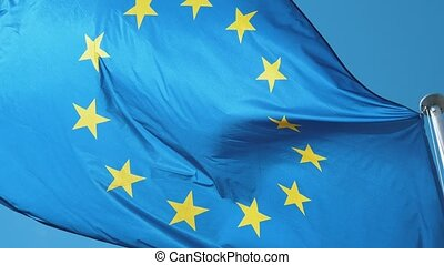 The EU flag flying in windy weather in a light blue sky in...