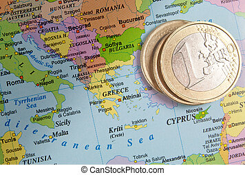 The euro and Greece - One euro coins next to a map of Greece