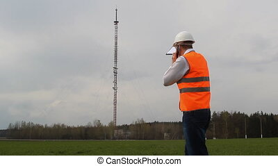 The evil chief engineer curses by telephone on the workers, against the background of a telephone tower