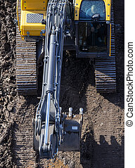 The excavator drives on the ground, leaving a tracked track. View from above. The front of the excavator is visible along with the bucket.