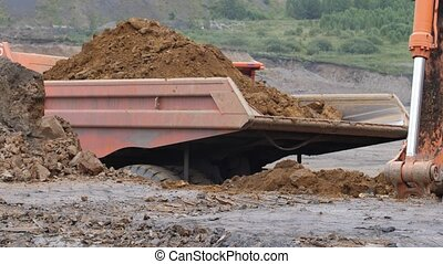 The excavator is digging the soil in close-up. Excavator loads the body of a dump truck. Excavator bucket rakes clay soil. Open pit mining.