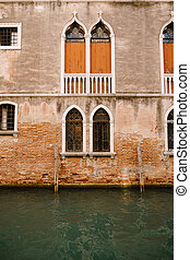 The facade of a corporatist apartment building in Venice, Italy. Buildings in waters of Venetian Canal. Typical Venetian windows with arches, columns and a sharp top, on the wall of a stone house.