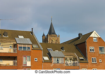 The facade of a modern building on the background of the church in Gorinchem, Netherlands