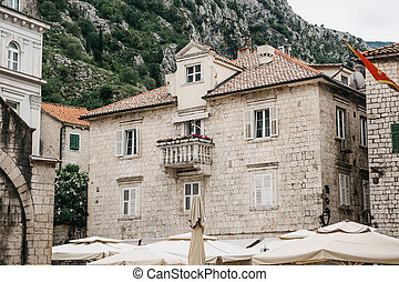 The facade of an ordinary old building with windows and a balcony in Montenegro.