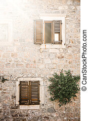 The facade of an ordinary old building with windows in Montenegro
