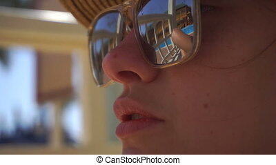 the face of a young girl in the glasses through which can be seen swimming pool