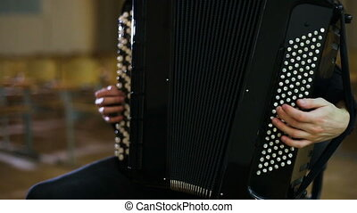The face of the accordionist. Fingers of accordionist on the keys