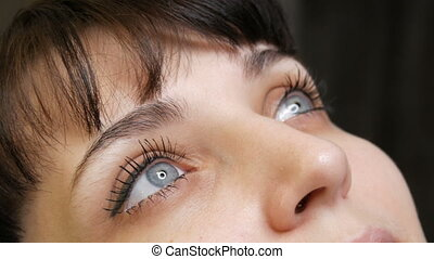 The face portrait of a beautiful young woman with blue eyes and long eyelashes before the procedure of permanent make up by microblading with eyebrow tattoo lies on a couch in a beauty salon..