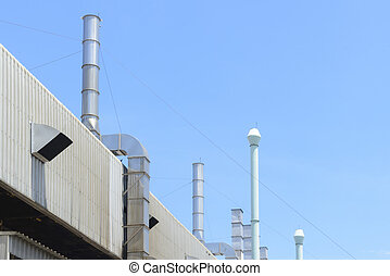 The factory building and the smoke stack with the blue sky. Industrial building