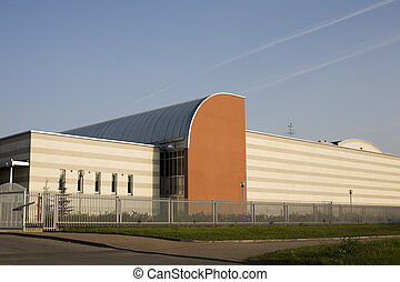 The factory - industrial solid building with a metal fence...