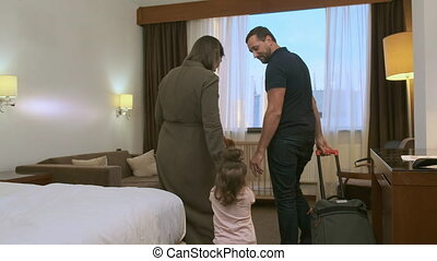 The family enters the hotel room with a suitcase. They ...