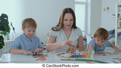 The family has fun painting on paper with their fingers in paint. Mom and two children paint with fingers on paper