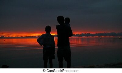 the family is looking into the distance at sunset as the sun goes down