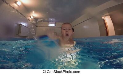 The family is swimming in the pool. A little son with his father happily enjoys bathing.