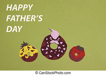 The family of chocolate donuts cut out of colored paper on a green background