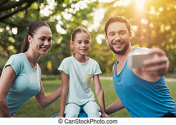 The family rests in the park after playing sports. A man does selfie with his family