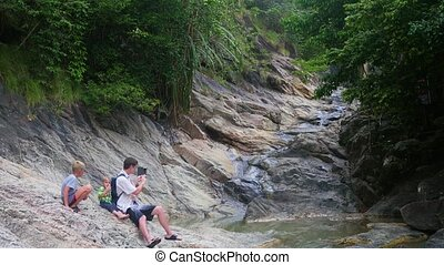 the family sits on the shore of a mountain river. makes a photo on a smartphone