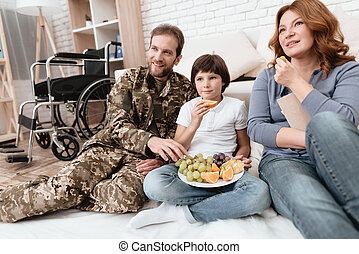 The family spends time together. A disabled father in military uniform is eating fruits with his family.