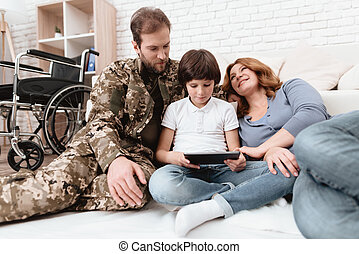The family spends time together. A father in military uniform rests with his son and wife.