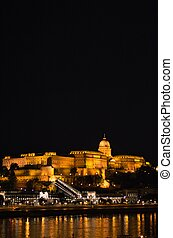 The famous Buda castle illuminated at night shot across river Danube in Budapest, Hungary